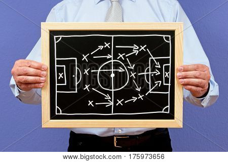Soccer trainer with tactics for game on chalkboard