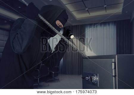 Picture of burglar stealing a safe deposit box using a crowbar while holding a flashlight in the office