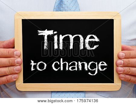 Time to change - Businessman holding chalkboard