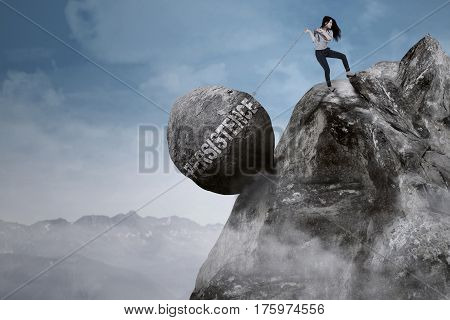 Image of beautiful female entrepreneur pulls big rock with persistence word while climbing on the mountain