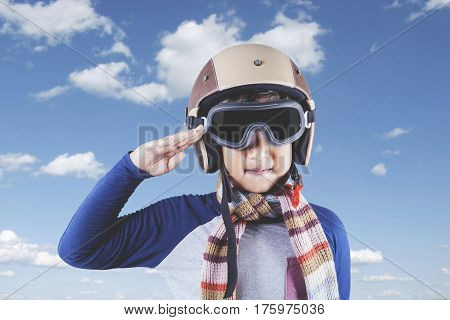 Portrait of a little boy wearing an aviator helmet while showing a saluting gesture under clear sky