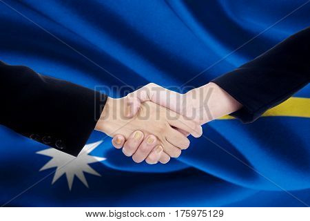 Photo of two businesspeople hands closing a meeting and shaking hands in front of Nauru flag