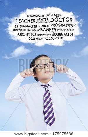 Portrait of elementary student wearing uniform school while concentrating to chooses his dream with a cloud bubble in the sky