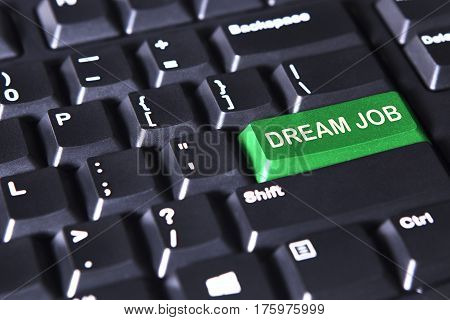 Picture of green button with text of dream job on the computer keyboard