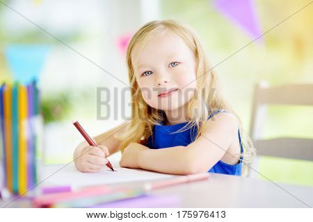 Cute Little Girl Drawing With Colorful Pencils At A Daycare. Creative Kid Painting At School