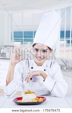 Image of a young Indian chef with a delicious dish on the plate while showing ok sign and smiling at the camera