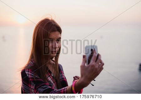 Portrait of young happy woman in hipster shirt standing in front of picturesque sea view, taking selfie with sunset or sunrise on smartphone.
