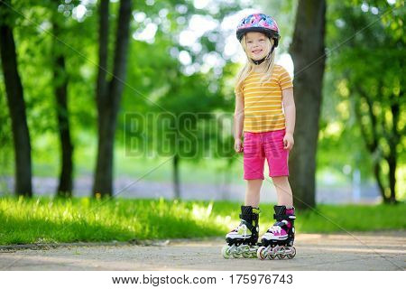 Pretty Little Girl Learning To Roller Skate On Beautiful Summer Day In A Park