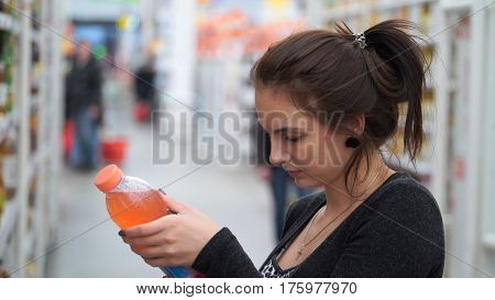 woman buys juice in supermarket or store