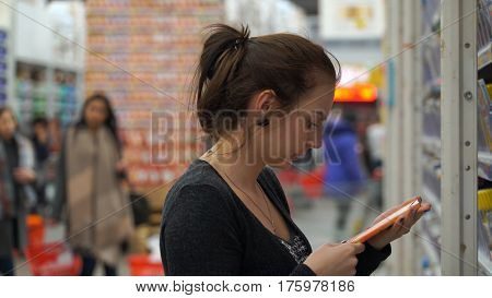 Woman buys chocolate in a supermarket or store