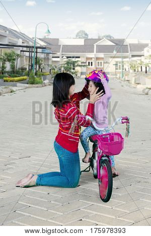 Image of Asian mother fasten a helmet on her daughter before riding a bicycle in the housing road
