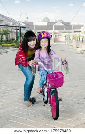 mage of beautiful mother teaching her daughter to ride a bicycle in the housing road