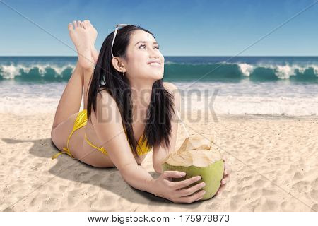 Pretty woman looking something while lying with a coconut drink on the beach