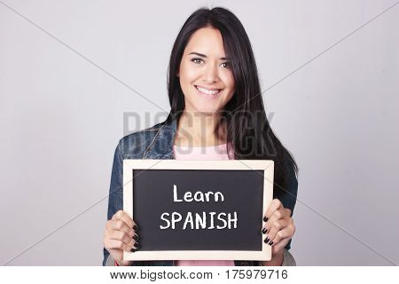 Young Woman Holding Chalkboard That Says Learn Spanish