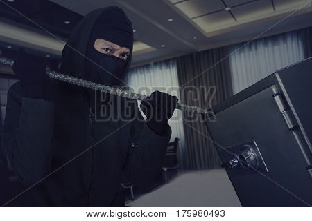 Male thief wearing a mask and trying to open a safe-deposit box in the office