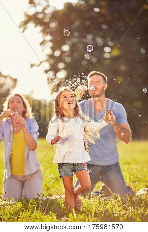 Fun for female child with colorful soap bubbles outdoor
