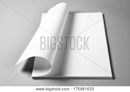 Blank sheets of paper with curled upper page, selective focus