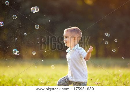 Cheerful childhood, male child chase soap bubbles
