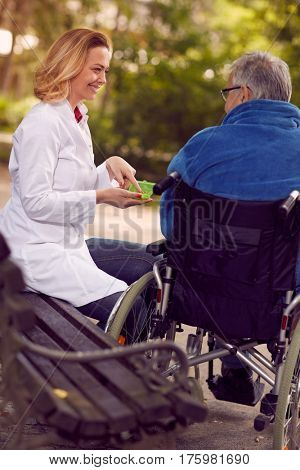 Hospice nurse giving medicine to senior man in wheelchair outdoor