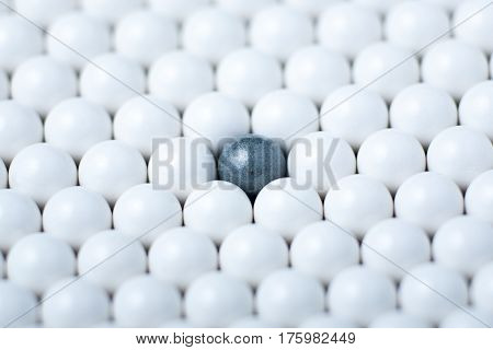 Black Bulb Among Many White Ones. Background Of Airsoft Balls