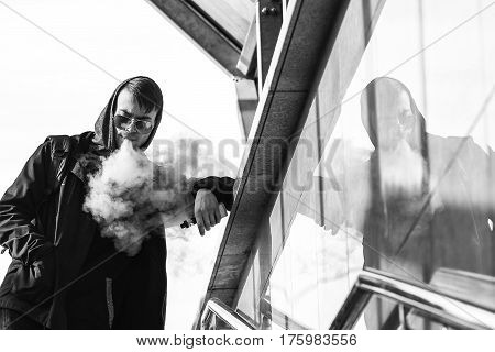 Vape. A Handsome Young White Guy In Sunglasses And In The Hood Is Standing And Smoking An Electronic
