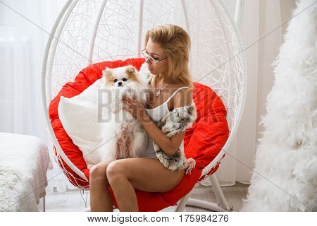 Beautiful girl sexy blonde in lingerie posing in the bathroom with the dog