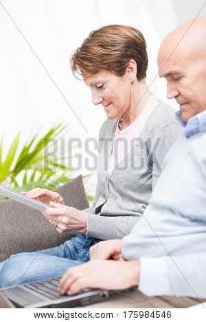 Tech Savvy Couple With A Laptop And Tablet