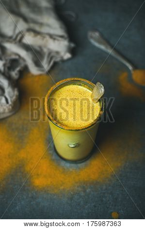 Golden milk with turmeric powder in glass over dark grunge background, copy space. Health and energy boosting, flu remedy, natural cold fighting drink. Clean eating, detox, diet, weight loss concept