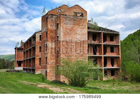 Unfinished brick building in Carpathian mountains. Summer.