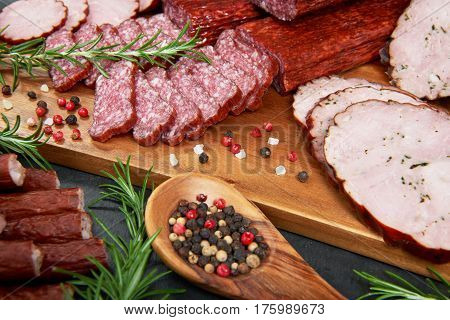 Set of cold cuts on a wooden board. Mix of sausages