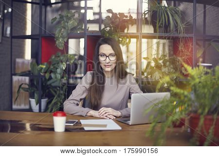 Beautiful girl wearing eye glasses in coworking studio. Using laptop and smartphone at the wooden table. Concept of young people working with mobile gadgets. Modern office blurred on background. Horizontal