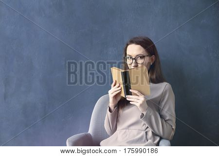 Beautiful businesswoman sitting in loft office reading vintage book. Look into opened book brown cover. Dark blue wall background day light