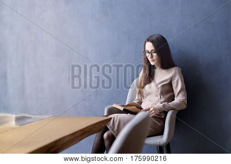 Beautiful businesswoman with long hair reading a book while sitting in his modern loft office. Dark blue wall background day light