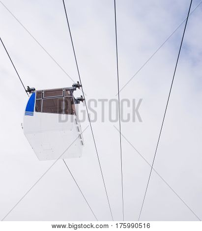 White and blue cable car against a cloudy sky