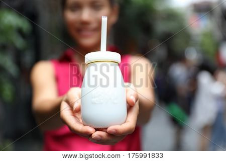 Traditional Beijing yogurt. Typical local street food of China, bottle of dairy drink. Travel lifestyle woman showing chinese dairy product.
