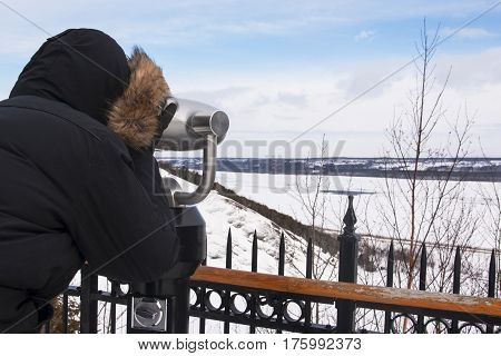 Man looking through a coin operated binocular at the St Laurent river during winter Quebec, Canada