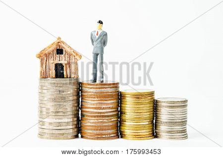 Miniature businessman with little home model on many stack of coins money on white background.