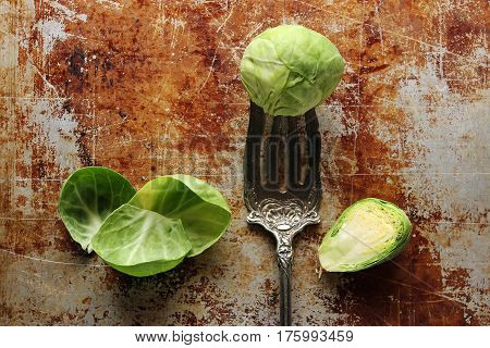 Brussel sprout rests on a vintage fork against tarnished baking sheet with pieces of leafy greens surrounding it.