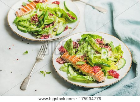 Healthy energy boosting spring salad with grilled salmon, blood orange, olives, cucumber and quinoa, selective focus, marble background. Clean eating, dieting, detox, weight loss concept