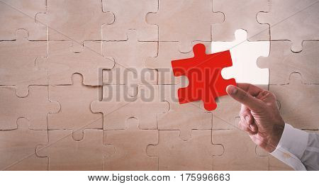 Businessman complete a puzzle inserting a missing piece