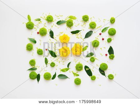 Pattern with roses, petals of chrysanthemum flowers, ficus leaves and ripe rowan on white background. Overhead view. Flat lay.