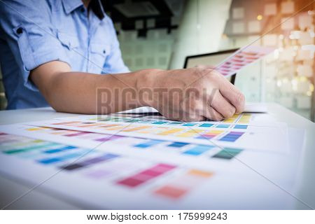 Graphic designer working choosing pantone in office