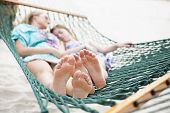 Barefoot and Relaxed family napping in a hammock together. Selective focus of two sets of feet relaxing in a comfortable hammock.  Looking at the bottom of there feet poster