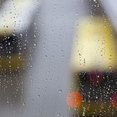 raindrops on glass pane and out of focus busses poster