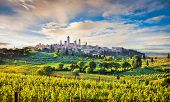 Classic view of the medieval town of San Gimignano and Tuscan countryside in golden evening light at sunset with dramatic clouds province of Siena Tuscany Italy poster