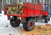 Red trailer with firewood attached to the tractor in the winter inwood or the park near place where tree has been cut. Side view from behind. poster