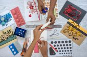 paperquilling art work. two multi-cultural female hands desinging paper quilling handycraft seen from top poster