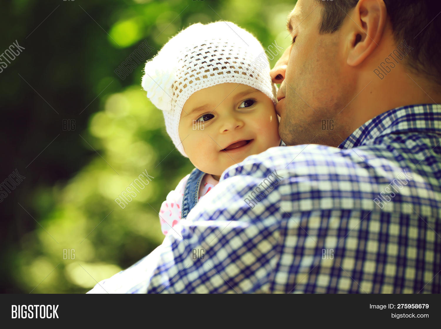 f5e688e4d21 ... small daughter baby girl cute hazel-eyed kid tiny little child wearing  white flower beanie hat outdoor on sunny summer day on blurred green  background