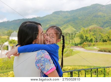 Asian Mother Carrying Daughter On Balcony At Hillside