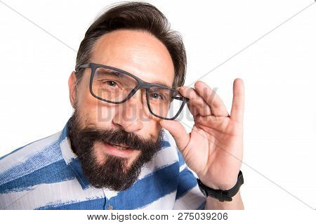 Interrogative Glance Of Smart Mature Man Looking At You While Touching The Rim Of His Glasses And Ke